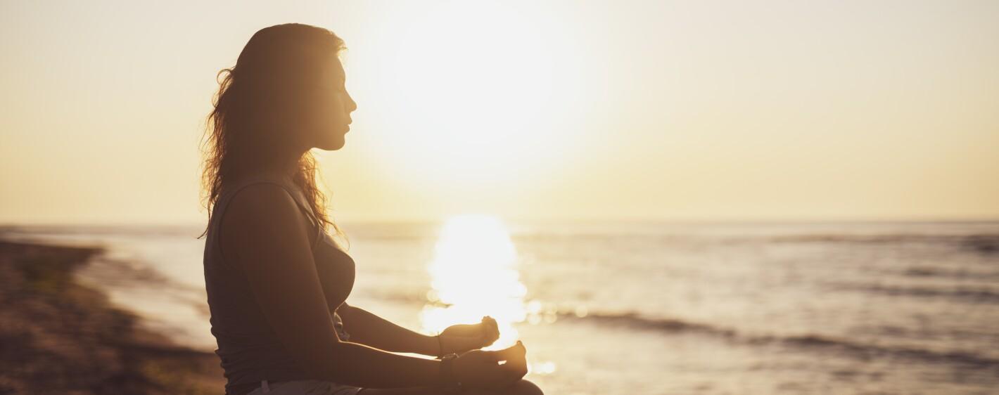 Woman meditation at sunrise.