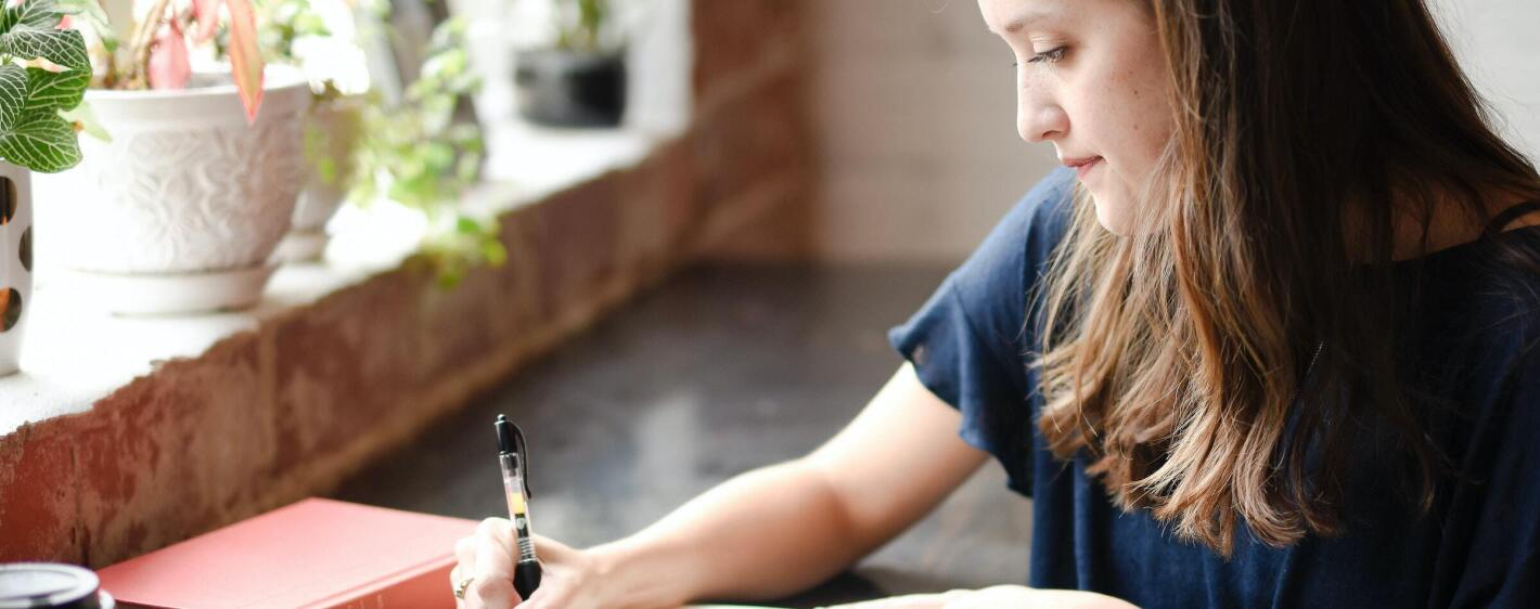 Woman sitting at table writing in notebook