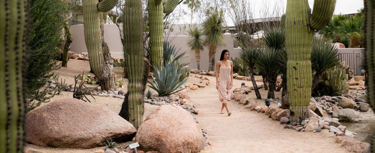 A young woman walking through a cactus garden