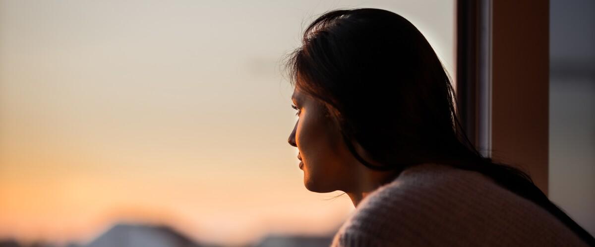 Young woman looking through window taking a break.