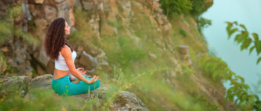 Woman meditating at a mountain ledge