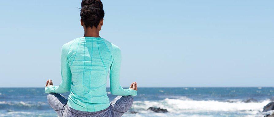 woman meditating back ocean
