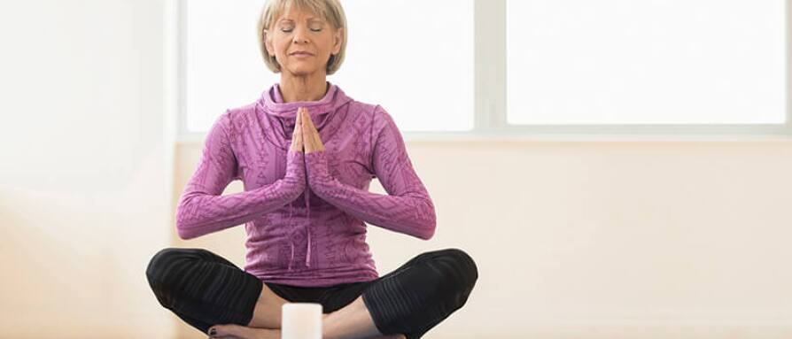 A  woman sitting in the middle of the room in meditation