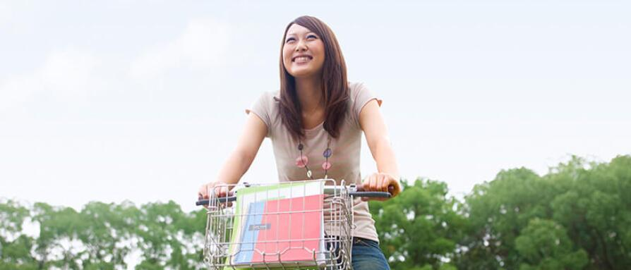 A young happy woman riding a bike with a smile